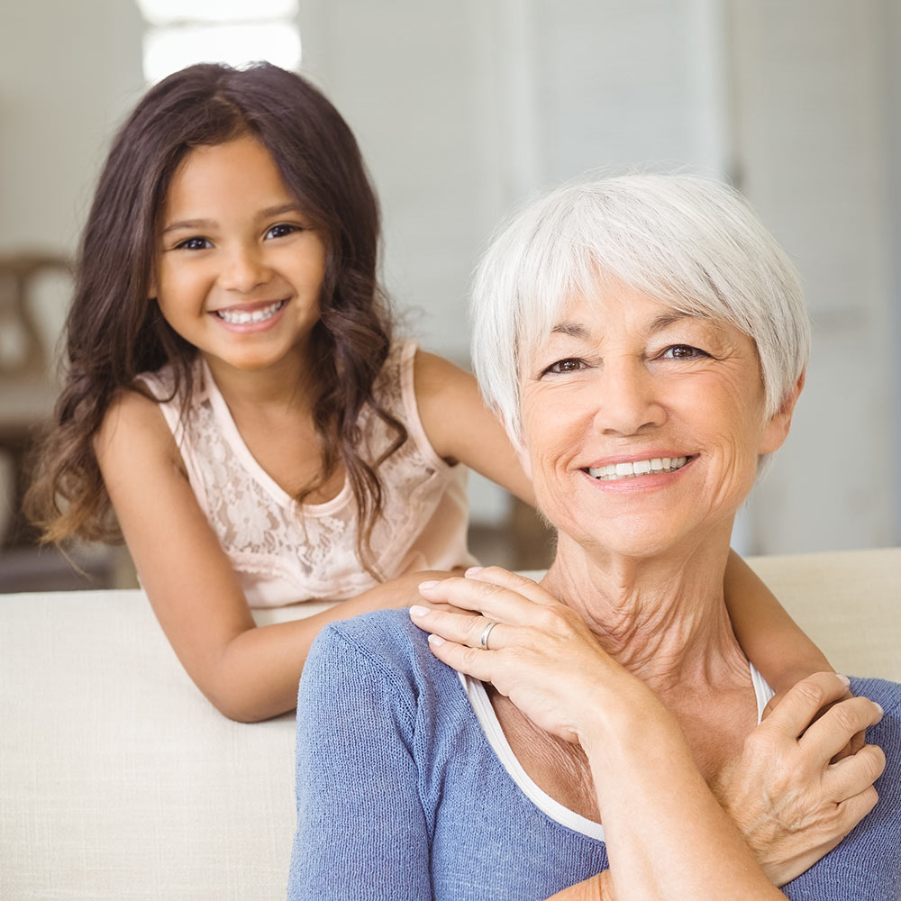 Portrait of smiling granddaughter embracing her grandmother in living room